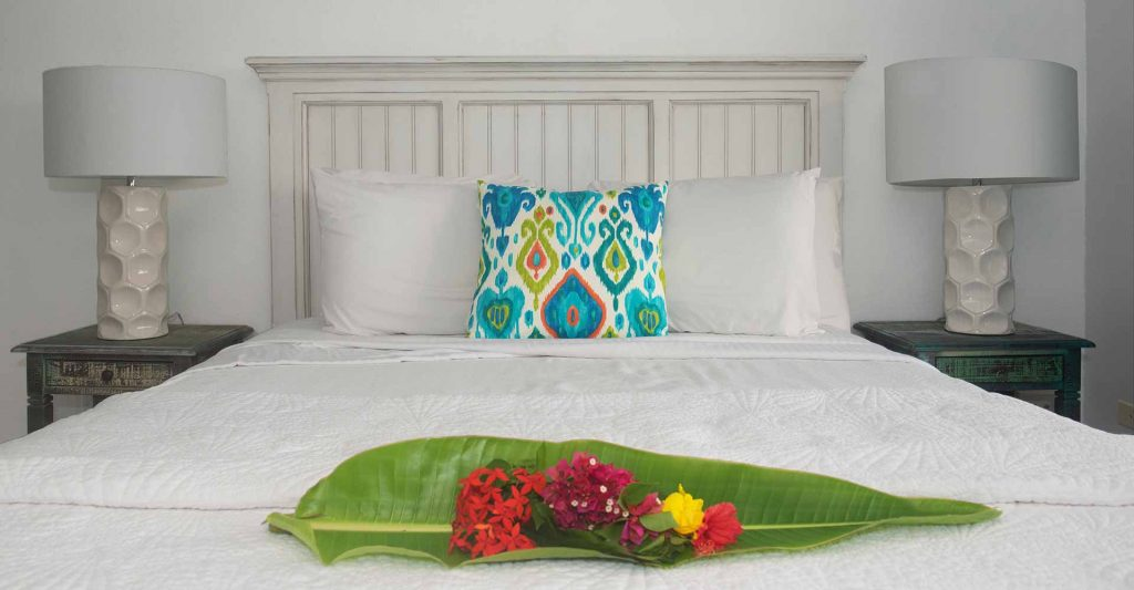 Queen bed in two bedroom suite with tropical flowers on the foot at Flamboyan on the Bay USVI