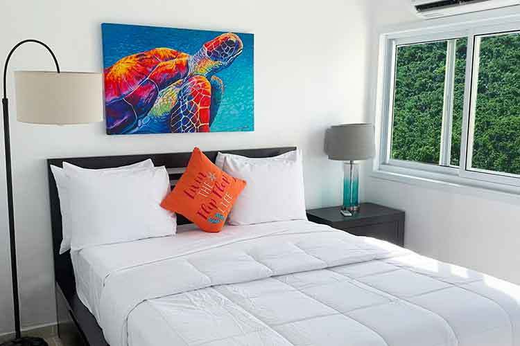 bed in two bedroom suite with turtle painting at Flamboyan on the bay