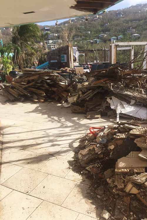 piles of debris with roof missing from building after IrMaria 2017