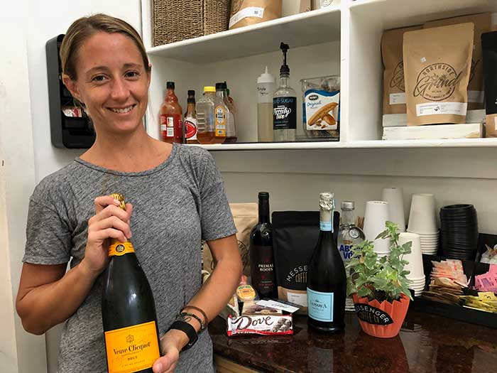 Trish Dahl, co-owner of Northside Grind, poses with a bottle of Veuve Clicquot