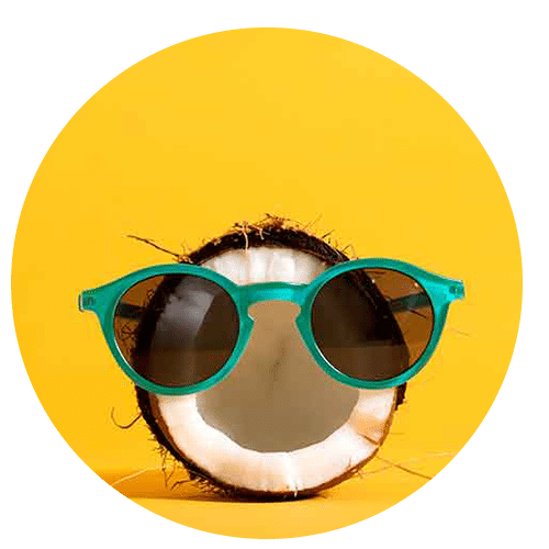 a round photo of a half of a coconut wearing teal sunglasses on a bright yellow background