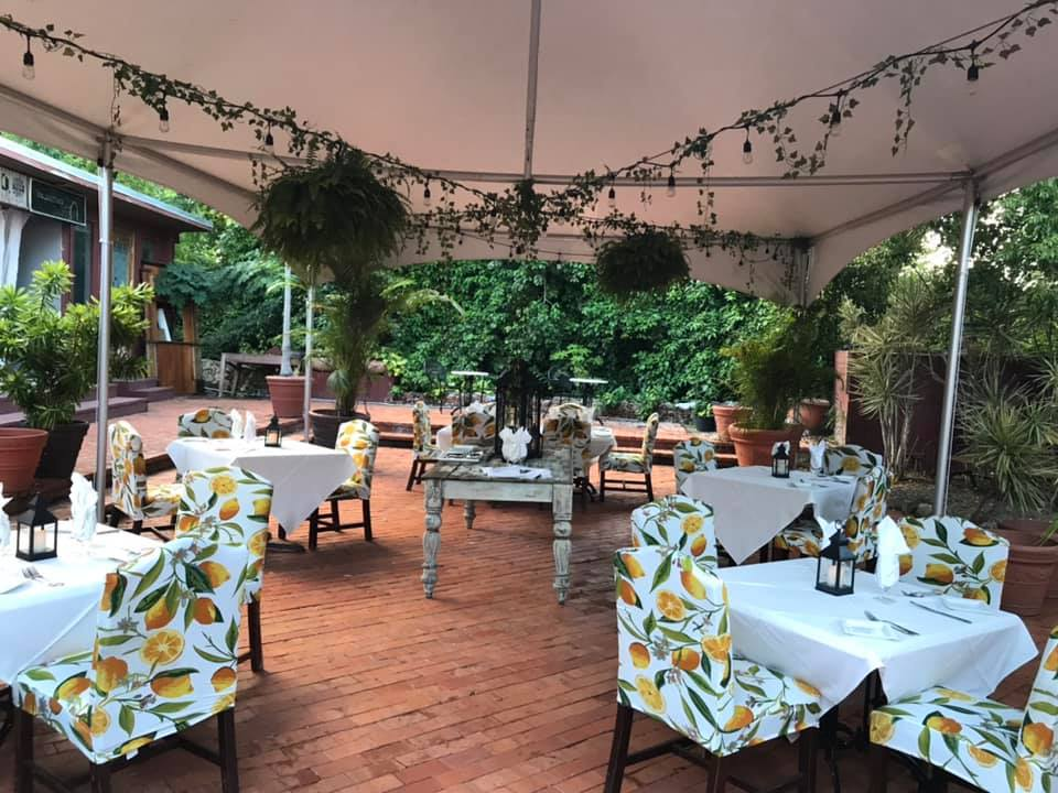 photograph of the patio at Old Stone Farmhouse and it's outside dining tables draped with white cloth and padded chairs featuring lemons and leaves print