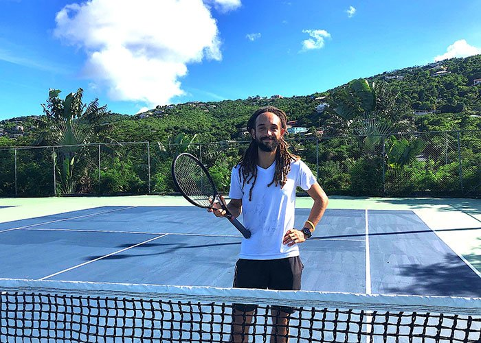 Coach John Hairston posing with his tennis racket on the tennis courts at Flamboyan on the Bay