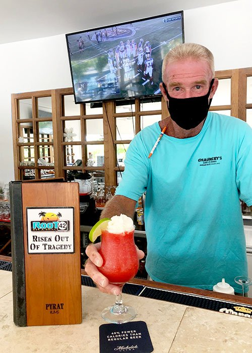 bartender holding out a frozen drink with a tv in the background showing a football game.