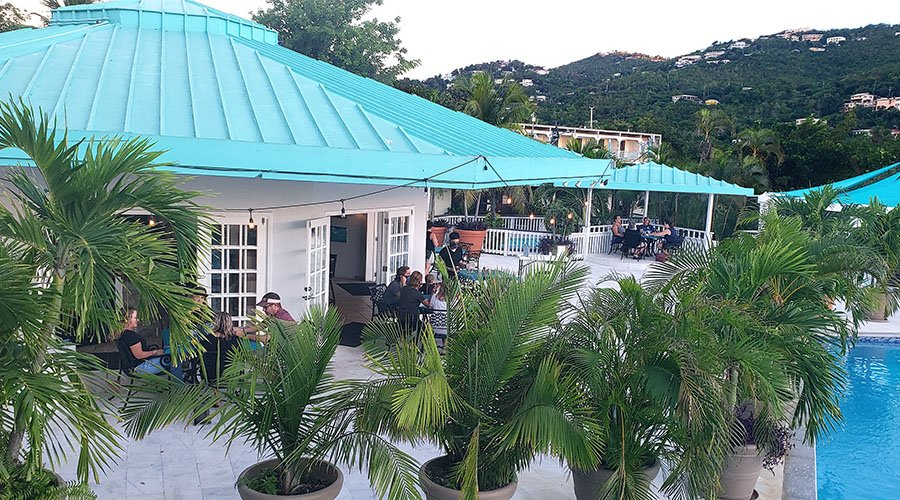 the poolside at root 42 bar & grill with diners eating under the canopy