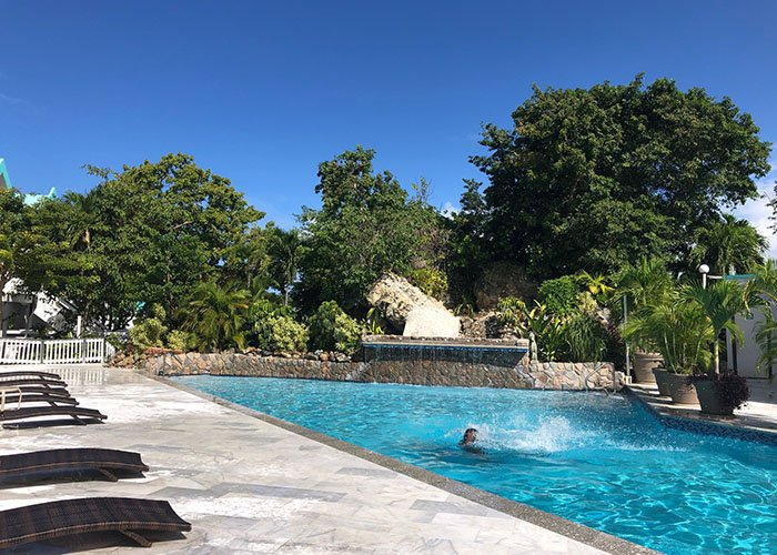 a person swimming in the Magens View Pool at Flamboyan on the Bay