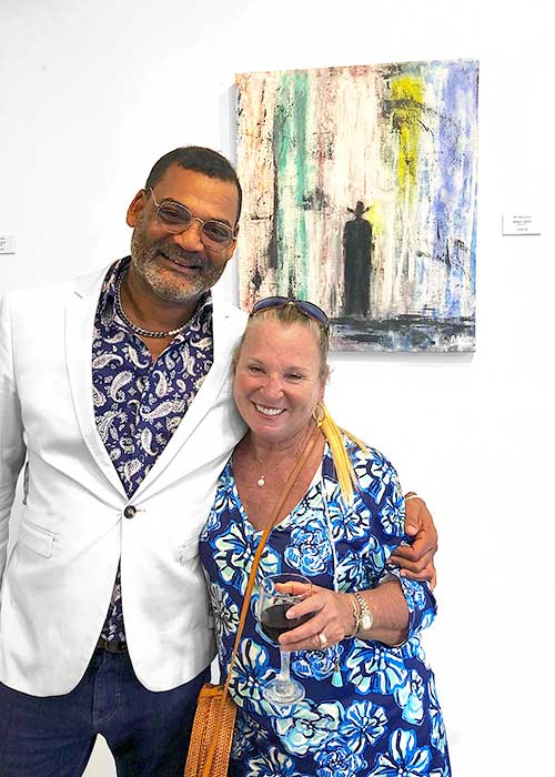 At a recent exhibit artist Augustin Holder poses with Flamoyan Resort's General Manager, Lori Baskin in front of one of his paintings
