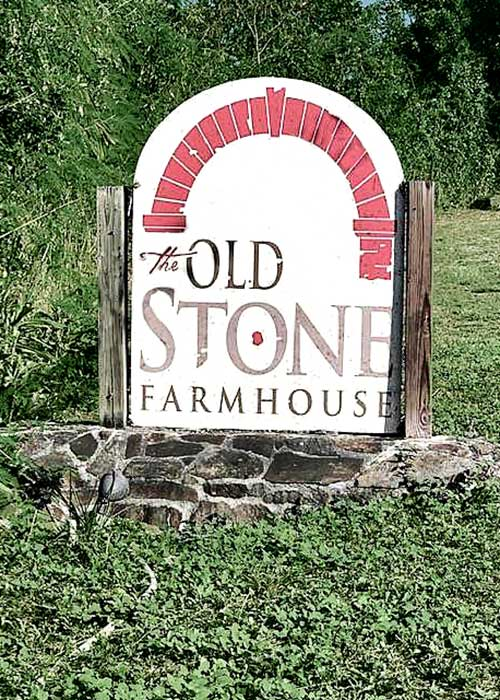 sign on the roadway for the old stone farmhouse surrounded by grass