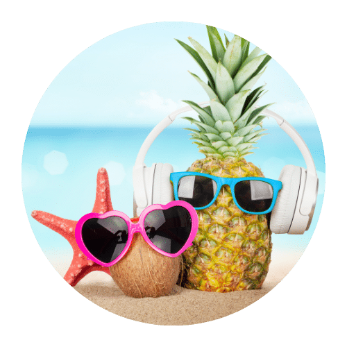 image of a coconut and pineapple both wearing sunglasses on a beach