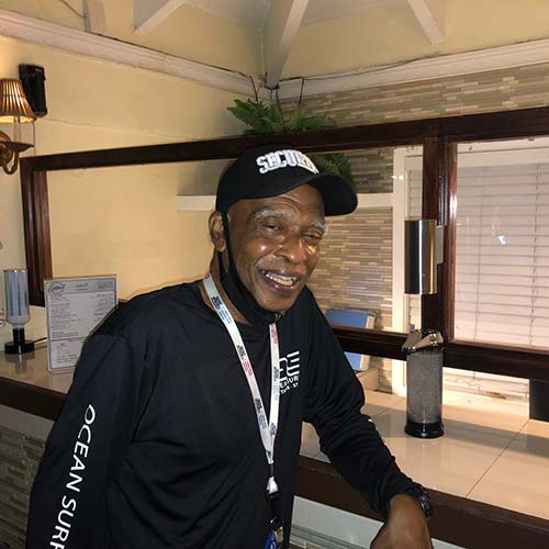 A man named Mr. Creque smiles poses for the camera with his arm leaning on the front desk of Flamboyan on the bay lobby