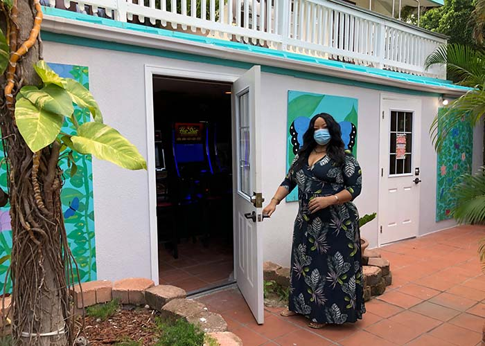 a woman in a long black dress with long dark hair wears a mask and is holding the door open to the VLT gaming room at Flamboyan on the bay