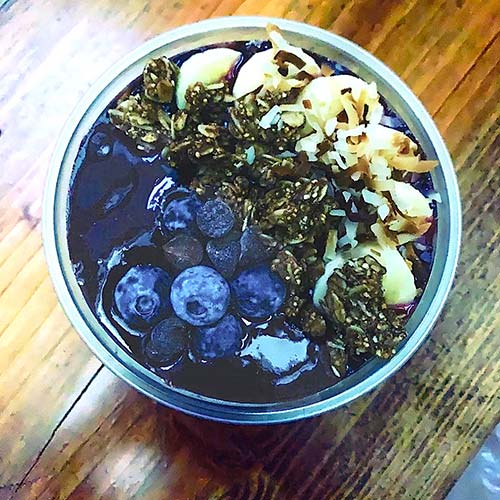 a breakfast bowl containing blueberries and granola is seen from the top down on a wooden table