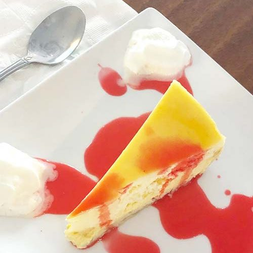a square white plate holds a piece of cheesecake topped with a berry couli and whipped cream rosettes a spoon sits on a napkin on the site