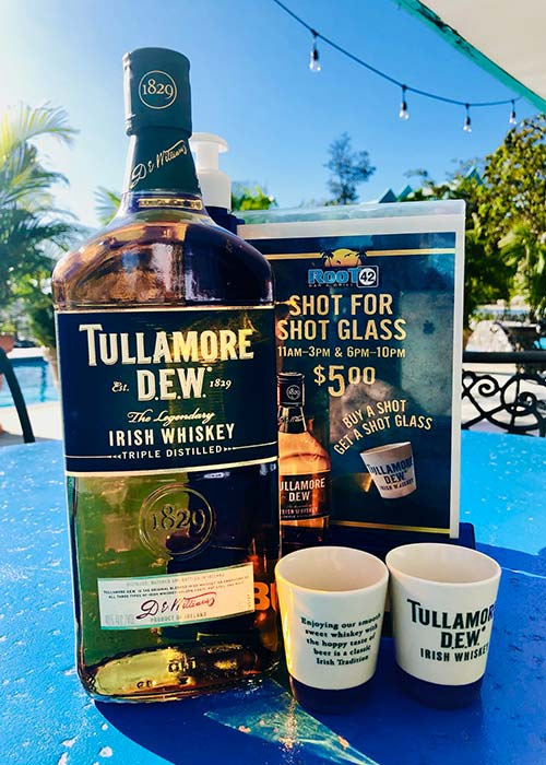 a bottle of tulamore dew sits on a blue table top in front of two shot glasses and a promo card featuring st Patricks day drink specials
