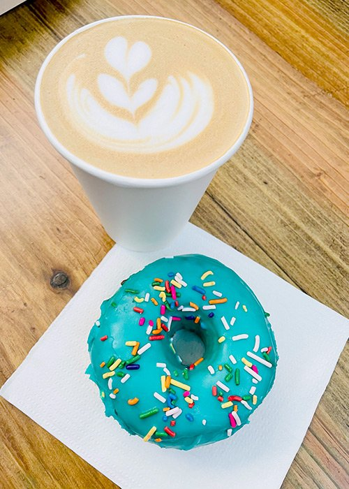 photo from above of a cappucino and a donut iced with turquoise frosting and sprinkles