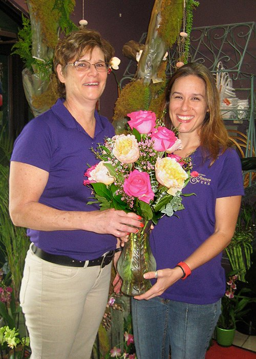 The owner of Forever flowers flower shop and daughter and stand with a bouquet of multi colored roses