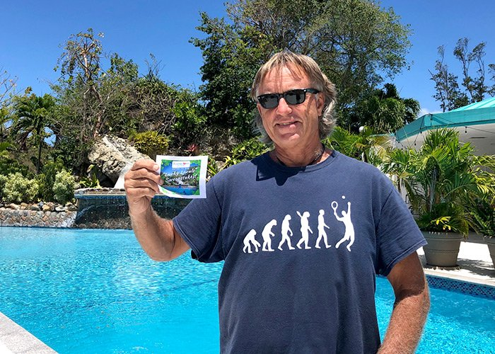 a man stands in front of a pool holding his winning ticket
