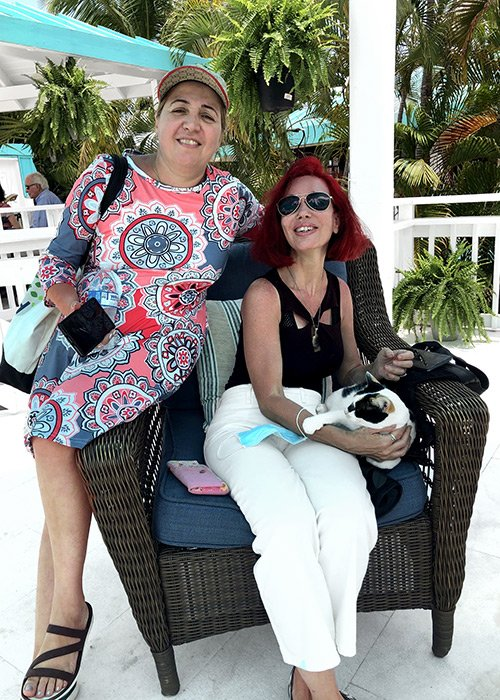 two woman sit on a chair while holding a flamboyan feline named diva