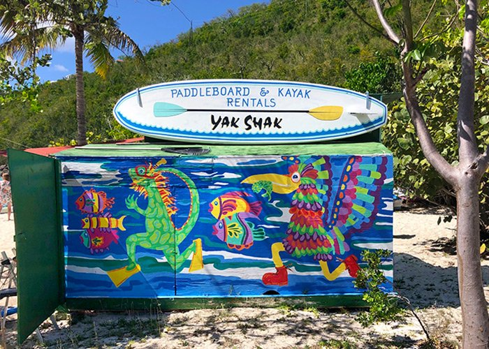 the yak shak sign sits atop a brightly painted box painted with birds, fish and an iguana wearing a snorkel mask