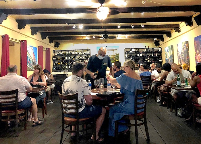 a packed dining room of diners at french quarter bistro. A waiter stands pouring wine for a couple in the center of the room