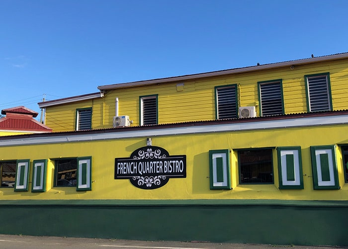 the exterior view of French Quarter Bistro the walls are painted bright yellow and the trim is a an emerald green