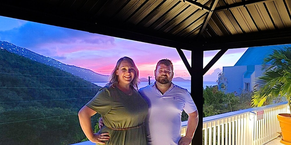 a couple poses on the deck of flamboyan on the bay resort with Magens bay in the background with a brilliant sunset