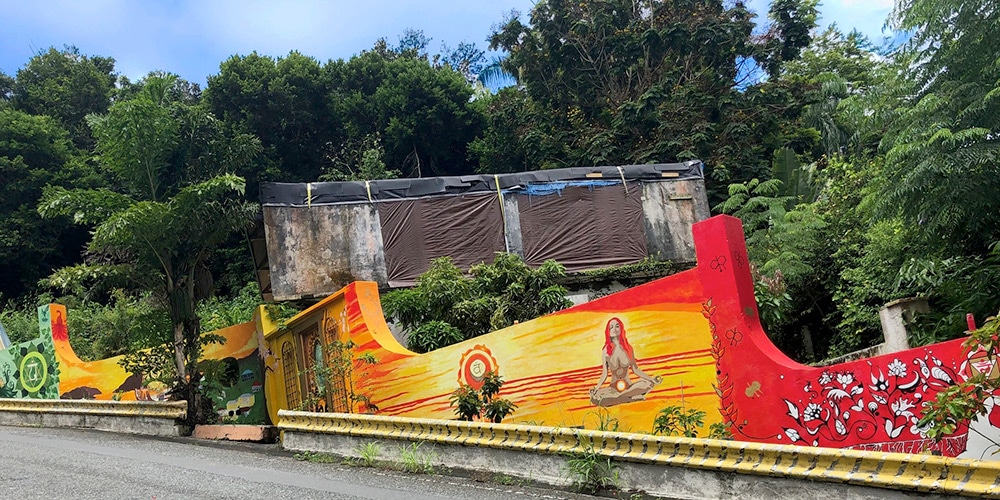 a mural on the long wall next to the road the mural is red and yellow and features a sunset, a woman meditating, island views and om symbols