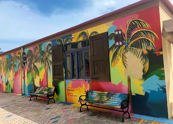 a multi colored abstract mural with palm trees lining the front of the building the colors are then added to some of the bricks on the ground