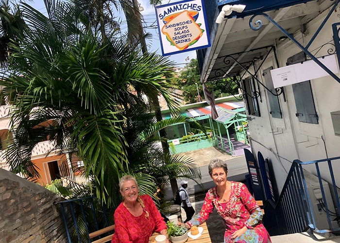 two woman sit outside at sammiches, a deli in charlotte amalie