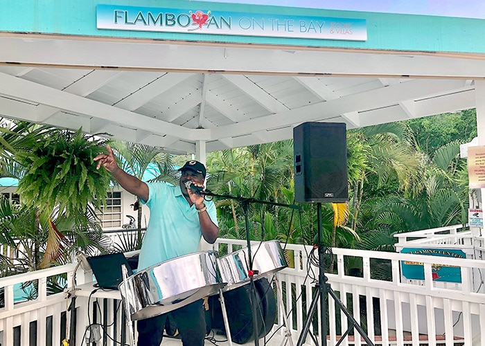 steel pan musician and vocalist Andrew Douglas performs on the pool deck at flamboyan on the bay