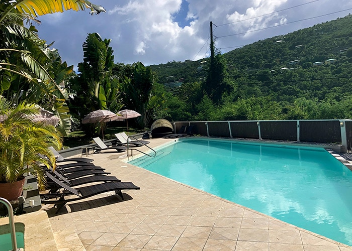 lower pool at flamboyan on the bar with lounge chairs and a green hill in the background