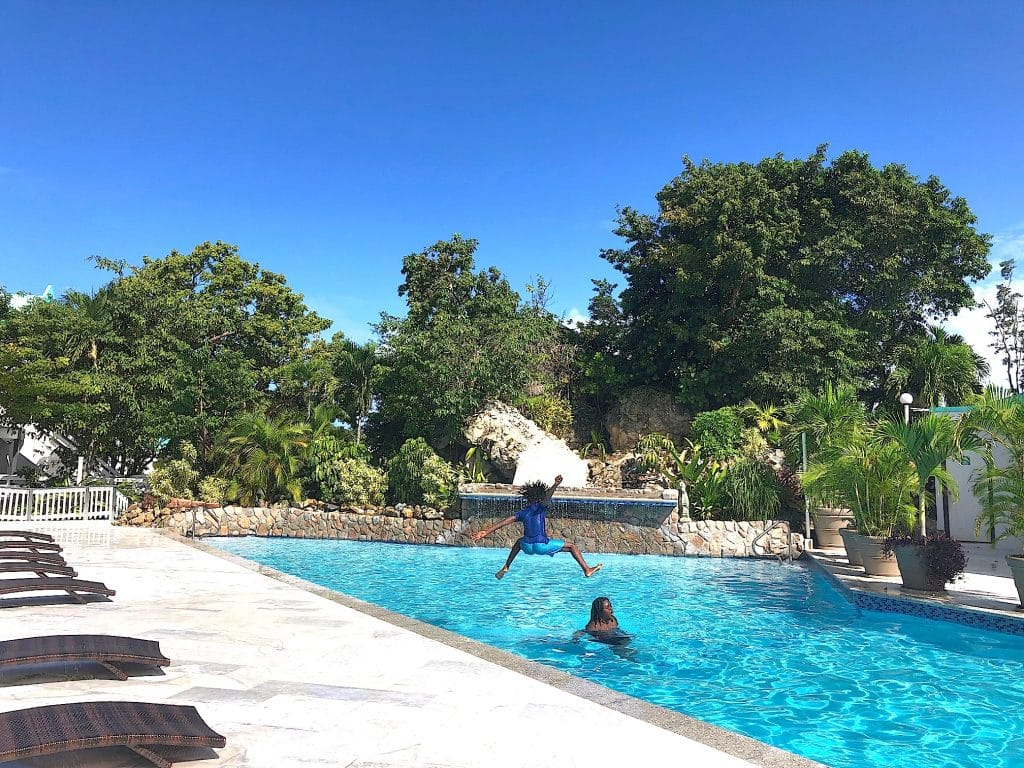 boy leaps into the air into the upper pool at flamboyan on the bay