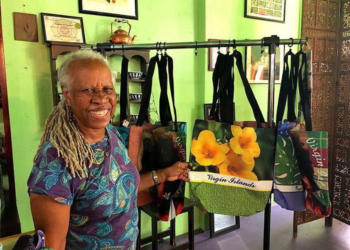 the owner of e's teahouse smiles at the camera showing a virgin islands bag